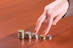 Pile di monete e di mano Immagine Stock
