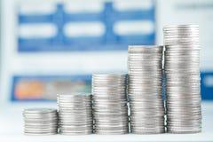 Pile di monete e di libro contabile o carta di credito sulla tavola di funzionamento Immagine Stock Libera da Diritti