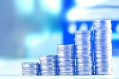 Pile di monete e di libro contabile o carta di credito sulla tavola di funzionamento Fotografia Stock Libera da Diritti