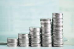 Pile di monete e di libro contabile o carta di credito sulla tavola di funzionamento Fotografie Stock