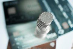 Pile di monete e di libro contabile o carta di credito sulla tavola di funzionamento Immagini Stock