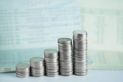 Pile di monete e di libro contabile o carta di credito sulla tavola di funzionamento Fotografia Stock