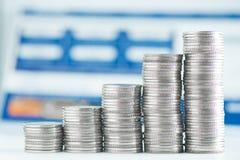 Pile di monete e di libro contabile o carta di credito sulla tavola di funzionamento Immagini Stock Libere da Diritti