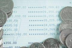 Pile di monete e di libro contabile o carta di credito sulla tavola di funzionamento Immagine Stock
