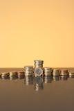 Pile di monete sopra con un'incandescenza dorata Fotografia Stock