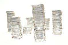 Pile di monete su bianco Immagine Stock