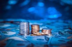 Pile di monete sui precedenti di cento banconote in dollari Luce blu scuro immagini stock libere da diritti