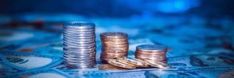 Pile di monete sui precedenti di cento banconote in dollari Luce blu scuro immagine stock libera da diritti