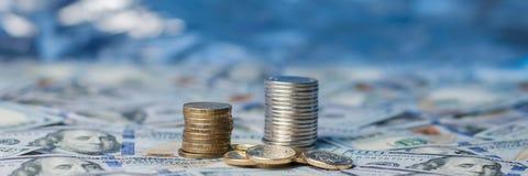 Pile di monete sulle note sparse di cento dollari fotografie stock