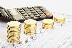 Pile di monete, un calcolatore di tendenza al ribasso sul grafico finanziario. Immagine Stock