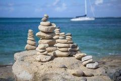Pile di pietre nell'equilibrio ad una spiaggia con l'yacht su fondo Fotografia Stock Libera da Diritti