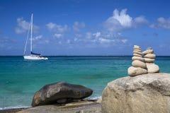 Pile di pietre nell'equilibrio ad una spiaggia con l'yacht su fondo Immagini Stock