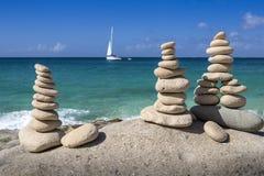 Pile di pietre nell'equilibrio ad una spiaggia con l'yacht su fondo Fotografia Stock