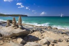 Pile di pietre nell'equilibrio ad una spiaggia con l'yacht su fondo Immagini Stock Libere da Diritti