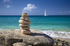 Pile di pietre nell'equilibrio ad una spiaggia con l'yacht su fondo Immagine Stock
