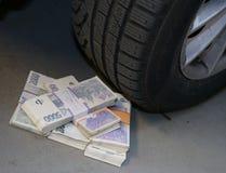 Pile di soldi davanti ad una ruota di automobile Fotografia Stock Libera da Diritti