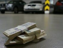 Pile di soldi su un pavimento in un garage dell'ufficio con le automobili nei precedenti Immagine Stock