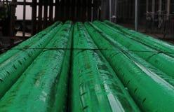 Pile di tubature dell'acqua verdi del PVC con acqua piovana immagini stock libere da diritti