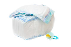 The pile of diapers and baby's dummy. Are isolated on a white background Royalty Free Stock Image