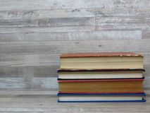 A pile of different coloured old books on bleached and whitewash beech wood background. White wood texture background. Wood planks, boards are old with a royalty free stock image