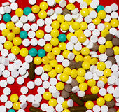 Pile of different pills on a red fabric background Royalty Free Stock Images