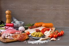 A pile of different Spanish embutido, like fuet, jamon, chorizo and lomo embuchado with spice and tomatoes cherry. Pile of different Spanish embutido, like fuet Stock Photo