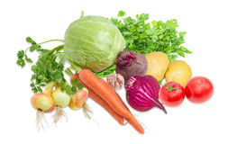 Pile of different vegetables and potherb on a light background. Pile of different raw vegetables and potherb, like white cabbage, tomatoes, onion, garlic Stock Photography