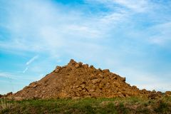 A pile of dirt. And rubble at a construction site on green grass with great blue sky royalty free stock photography