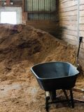 Pile of dirt with wheelbarrow and shovel. Large pile of Brown dirt soil inside of a horse barn used to coat the floor of a writing area. Black wheelbarrow and Royalty Free Stock Photo