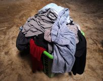 Pile of dirty clothes. In green basket on cement floor Royalty Free Stock Photography