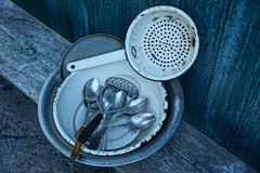 Pile of dirty dishes on a wooden board near a green wall in the street royalty free stock images