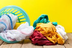 Pile of dirty laundry in washing basket on wooden,yellow backgro Stock Photo