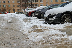 A pile of dirty snow on the parking near the cars in the yard Stock Image