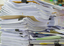 Pile of documents on desk stack up high waiting to be managed Royalty Free Stock Image
