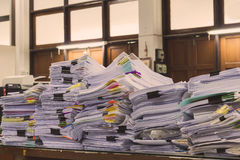 Pile of documents on desk stack up high. Waiting to be managed royalty free stock image