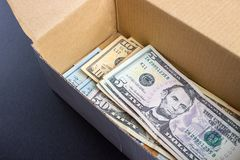 A pile of dollar bills lying in a box stock image