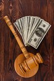 A pile of bills, a auctioneer`s hamme on a wooden table. A pile of dollar bills, a wooden auctioneer`s hammer and a stand on a wooden table. Details of the Stock Photo