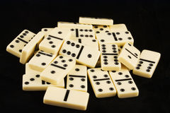 Pile of dominoes on black. Close up of pile of white domino pieces on black background Royalty Free Stock Photo