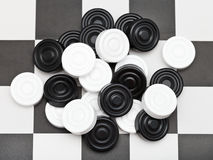 Pile of draughts on checkerboard Royalty Free Stock Image