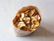 A pile of dried apples. A big pile of yellow dried apples in a paper bag on the table Stock Photography