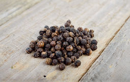 Pile of dried black pepper grain on table Stock Photo