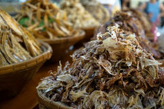 Pile of dried small squid in bamboo basket with dried fishes in blurred background in Nongmon market Stock Images