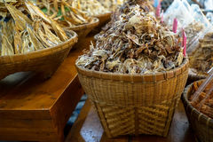 Pile of dried small squid in traditional bamboo basket with dried fishes in blurred background in Nongmon market Stock Photography