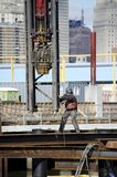 Pile Driver. A worker swings a pile driver into position on an urban construction site Royalty Free Stock Photos
