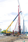 Pile driver works to set precast concrete piles for repair road Stock Image