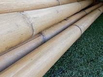 Pile of dry brown bamboo sticks with wooden texture over green astroturf on background. Pile of dry brown bamboo sticks with wooden texture in diagonal over Royalty Free Stock Photo