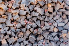 Dry stacked firewood with autumn leaves. Pile of dry gray stacked firewood with some autumn leaves Stock Photos