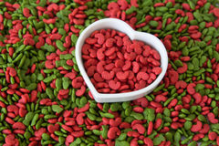 Pile of dry pet food with love. Pile of dry pet food with heart shape cup Royalty Free Stock Photos