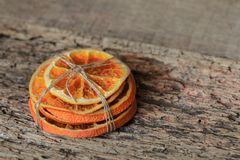 A pile of dry sliced Orange tied with a gray thread on a wooden table Stock Photography