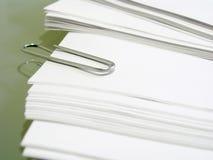 Pile du papier vergé blanc avec le trombone en métal image libre de droits